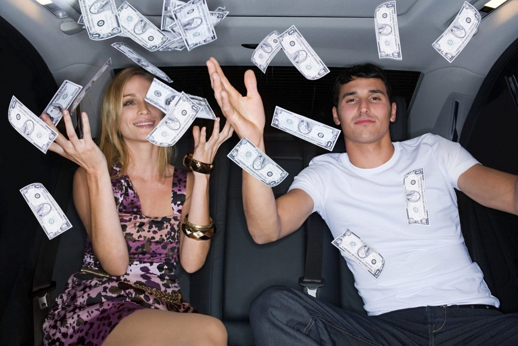 Wealthy couple celebrating in a car